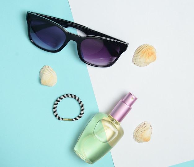 Female fashion accessories. sunglasses, perfume bottle, shells. summer beach accessories. top view, minimalist trend, copy space, flat lay.
