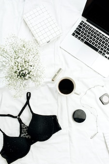 Female fashion blog concept with laptop, bra, coffee, flowers, cosmetics and accessories on white linen