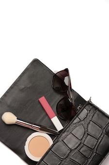 女性のファッションコンセプト:グレーの背景の上にプレストパウダー、マットな口紅、サングラスをドロップアウトしたレザーバッグ。テキスト用のスペース