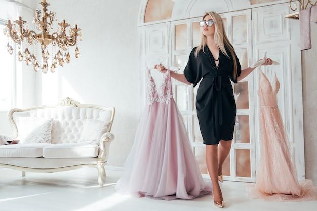 豪華なイブニングドレスを保持している女性のファッションコンサルタント。 vipブティック