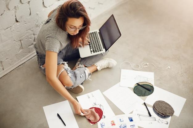 밝은 스튜디오 환경에서 랩톱에서 작업하는 여성 패션 디자인 학생 드로잉 스케치와 삽화. 평면도