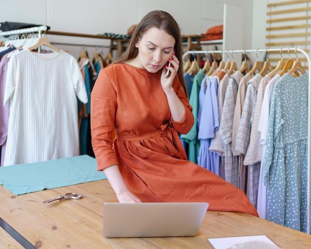 Женский модельер проверяет онлайн-заказ на ноутбуке во время разговора с клиентом по мобильному телефону
