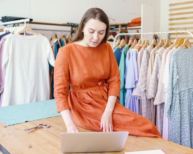 Модельер женского пола, создающая дизайн одежды онлайн на ноутбуке
