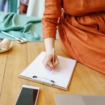 Модельер женского пола рисует эскиз нового модного платья в современном ателье
