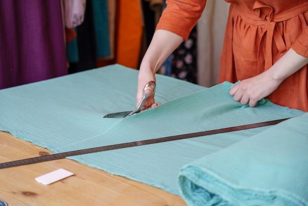 Женский модельер или портной кроят ткань на столе перед шитьем одежды в ателье