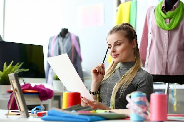 Female fashion designer sit at her office
