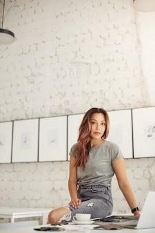 밝은 스튜디오 공간에서 커피를 마시는 노트북에서 일하는 여성 패션 디자이너. 젊은 재능이 그녀의 삶을 살아가고 있습니다. 카메라를 찾고 있습니다.