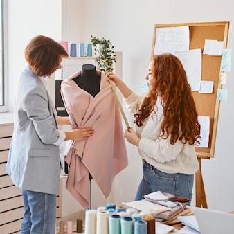 Stilisti femminili che lavorano nell'atelier e controllano l'indumento sulla forma del vestito