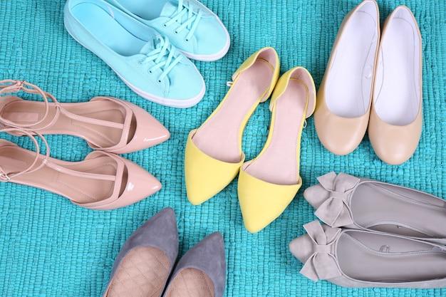青いじゅうたんの上の女性のファッション靴