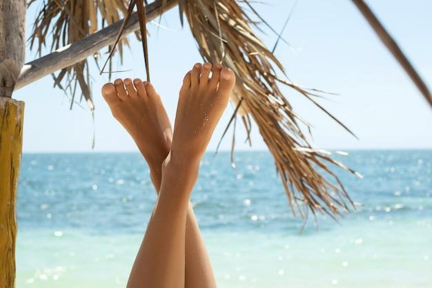 Female feet against background of the beautiful blue sea