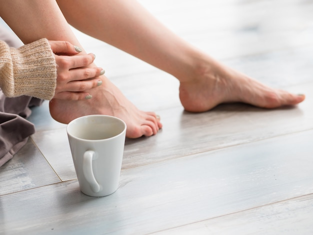 女性の足とお茶やコーヒー。コーヒータイムと覚醒のコンセプト