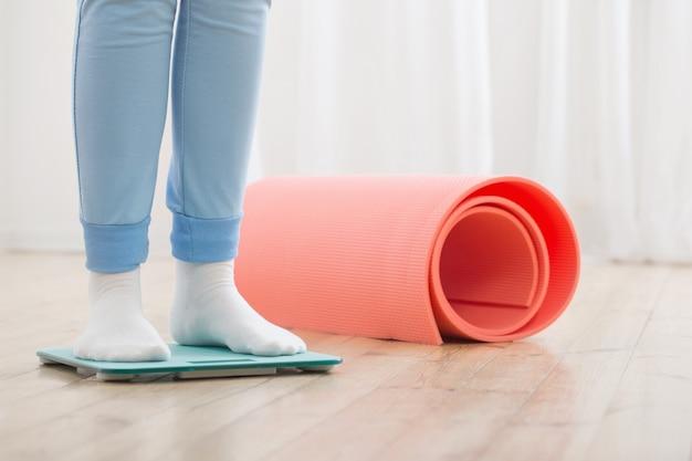 Женские ножки и весы для ванной на деревянном полу