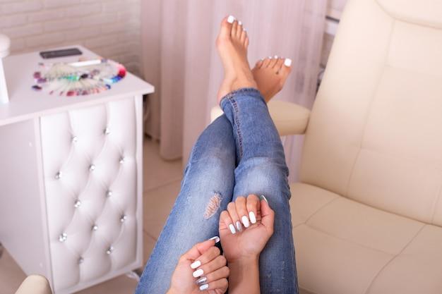 Женские ноги и руки со стильным маникюром и педикюром.