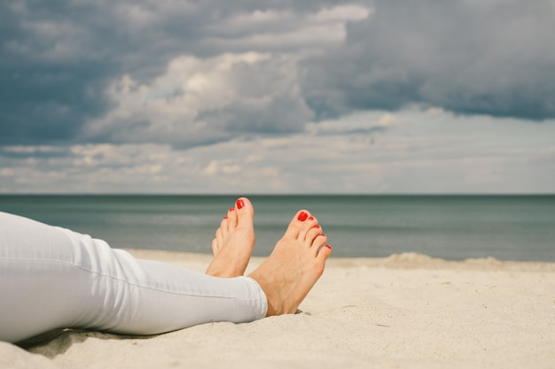 Female feet on the beach barefoot with red pedicure