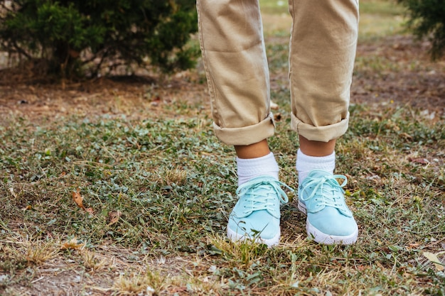 Female feet in beige pants and a turquoise sneakers standing on the grass near the trees