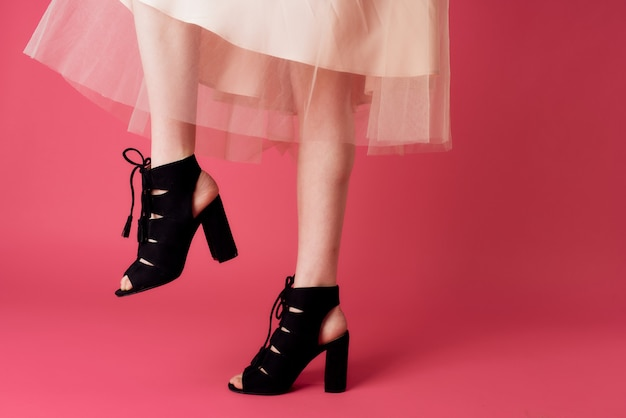 Female feet black fashionable heels shoes charm pink background. high quality photo