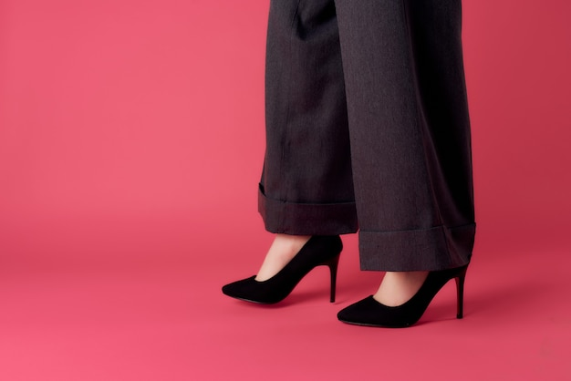 女性の足の黒い靴のトリミングされたビューピンクの背景モダンなスタイルの魅力