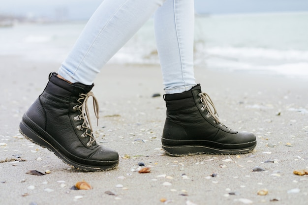 Female feet in blue jeans and black winter boots are on the beach sand