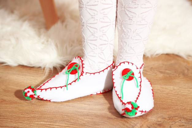 Female feet in decorative christmas shoes