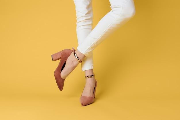 女性の足のファッショナブルな靴高級黄色の背景エレガントなスタイル