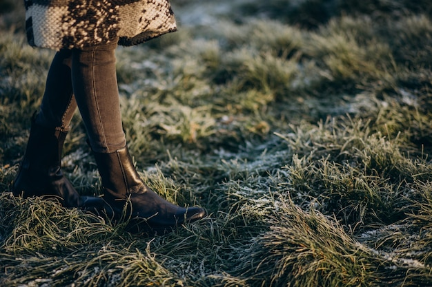 Female feet on the grass covered with hoarfrost