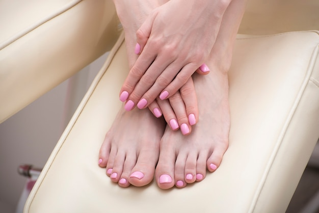 Female feet and hands with a pink manicure. beauty saloon. close-up