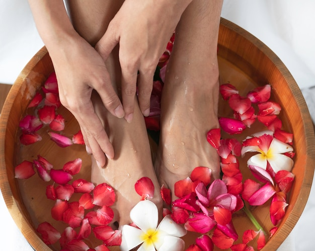 Female feet and hands  in  wooden bowl with flowers at spa salon.