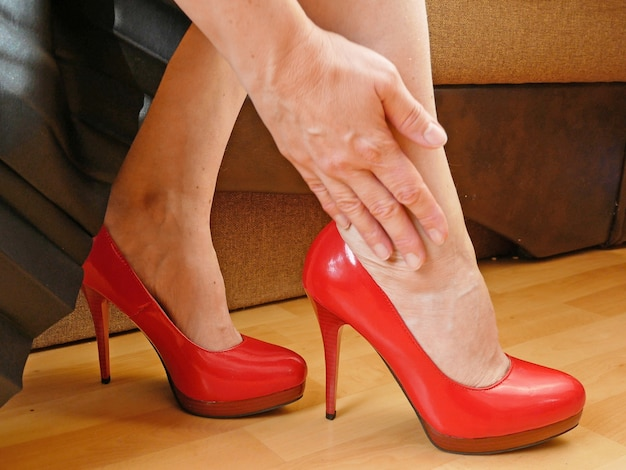Female feet and heels, woman's legs get tied of shoes with high hill, woman after party
