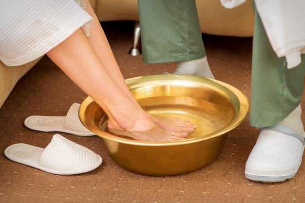스파 살롱 스파 트리트먼트에 물과 황금 그릇에 여성 피트