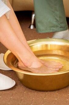 스파 살롱에서 물과 함께 황금 그릇에 여성 피트. 스파 트리트먼트.