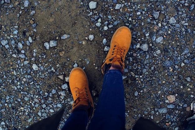 地面の自然の上面図のブーツの女性の足