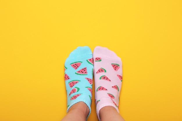 パステルイエローの背景にスイカのピンクとブルーの靴下の女性の足がプリントされています。上面図。コピースペース。