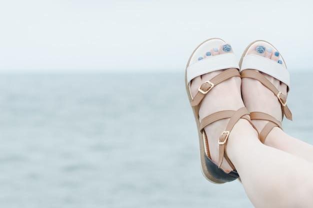Женские ножки в сандалиях с маникюром на фоне моря.