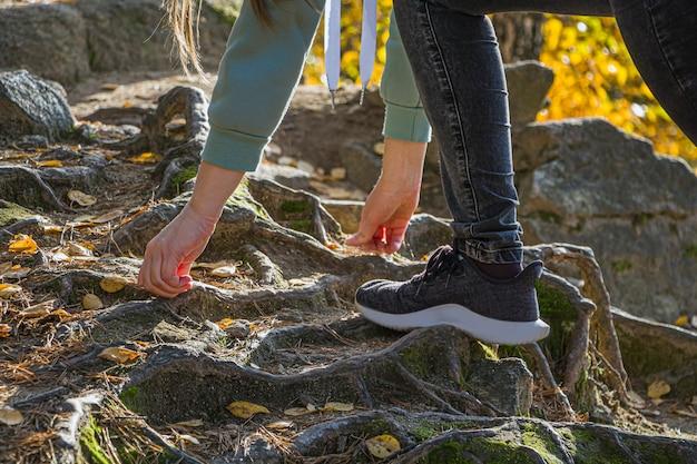 岩の上のスポーツスニーカーの女性の足。