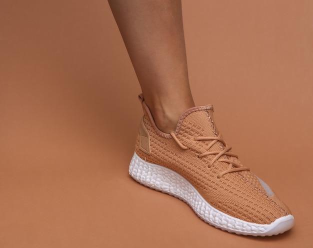 茶色の背景にトレンディなスポーツシューズの女性の足