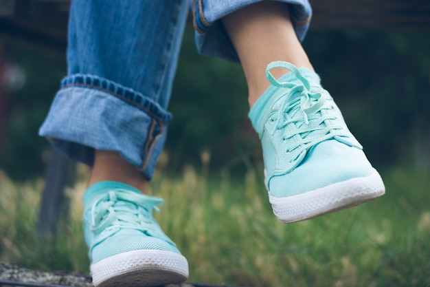 Female feet in jeans and sports shoes in the park close up