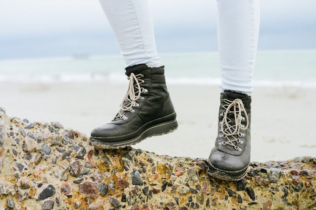 Female feet in jeans and winter boots standing on a stone on the coast close-up