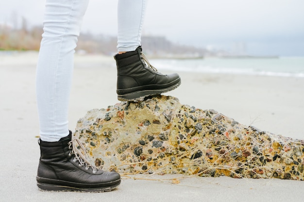Female feet in jeans and winter boots standing on a stone on the coast