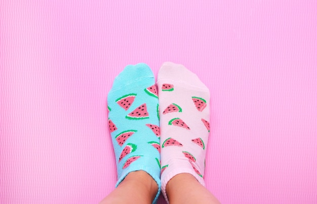 Female feet in pink and blue socks in watermelon print on a pastel pink background. top view.copy space. Premium Photo