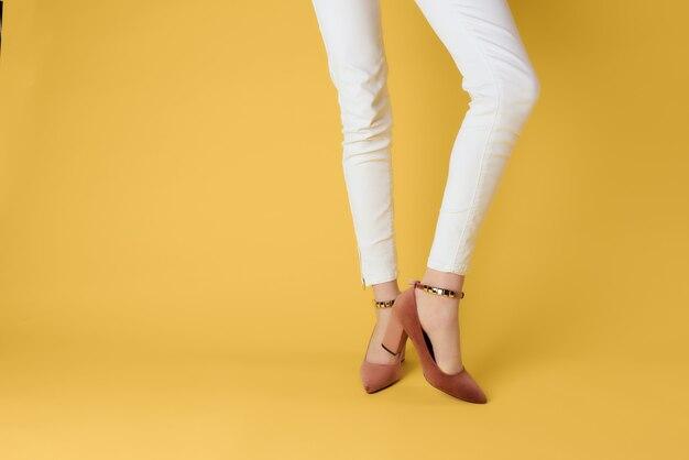 Female feet in posing shoes fashion season luxury yellow background