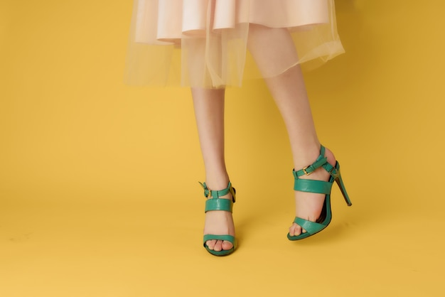 Female feet in shoes summer summer style yellow background fashion. high quality photo