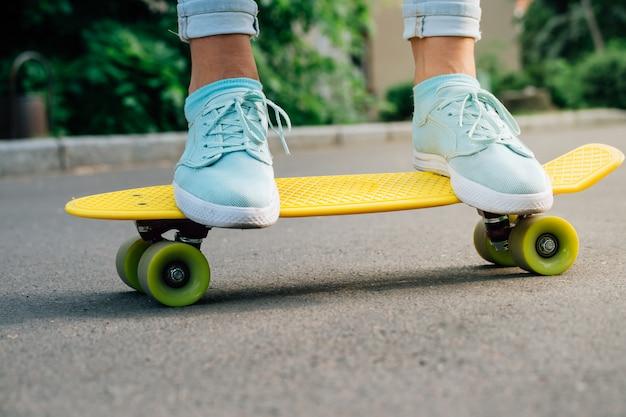 Female feet in sneakers on a yellow skateboard