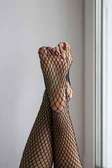 Женские ноги, подошвы и пальцы ног в черной сетке на фоне окна. концепция фут-фетиш.