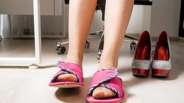 Female feet in stockings wearing comfortable slippers in office.