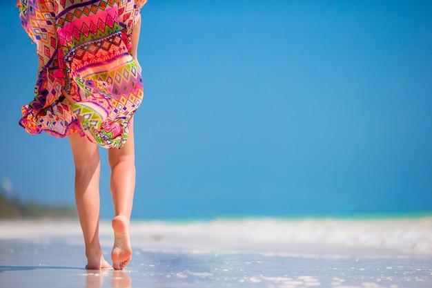 Female feet on white sandy beach.
