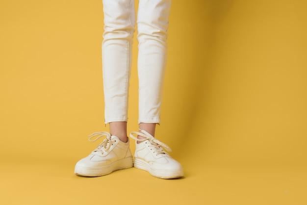 女性の足の白いスニーカーの魅力的な外観のファッション黄色の背景