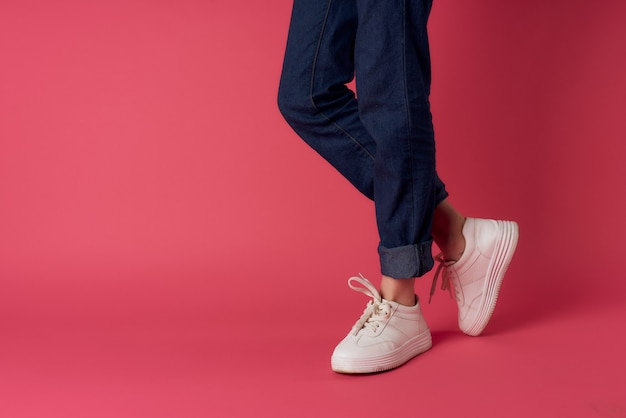 女性の足白いスニーカーストリートファッションピンクの背景