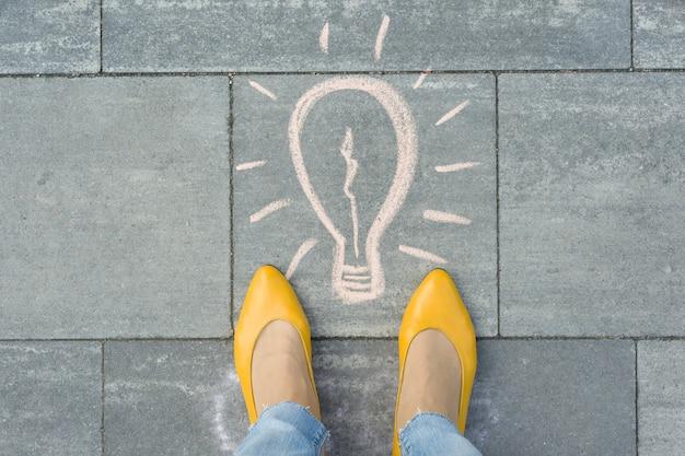 Female feet with drawing of light bulb written on grey sidewalk