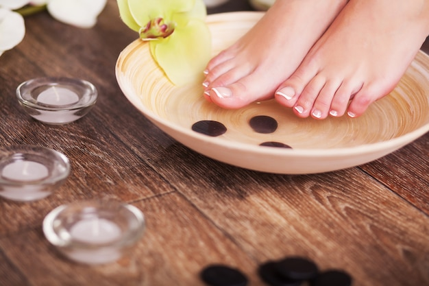 Female feet with drops of water, spa bowls, towels, flowers and candles.