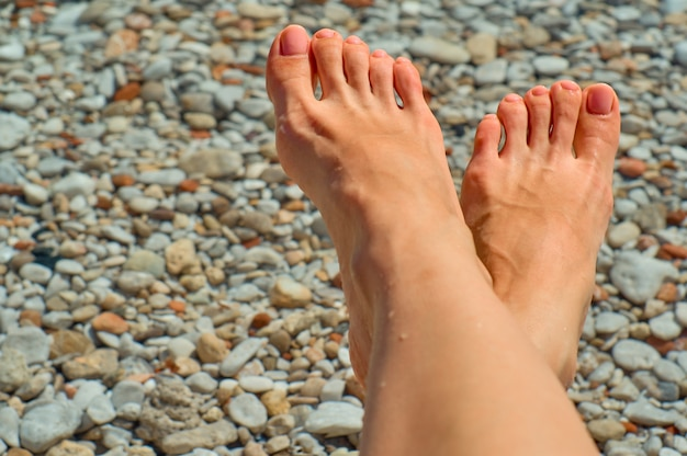 Female feet with a gentle pedicure with beach stones background